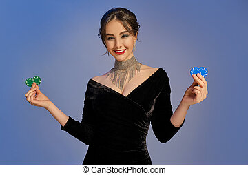 Brunette lady in black dress and shiny jewelry. Smiling, showing two blue and green chips, posing on purple background. Poker, casino. Close-up