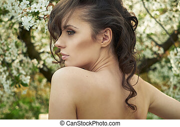 Brunette lady realxing in the orchard