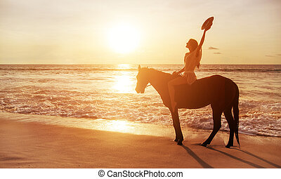 Brunette lady riding a horse alongside the coastline