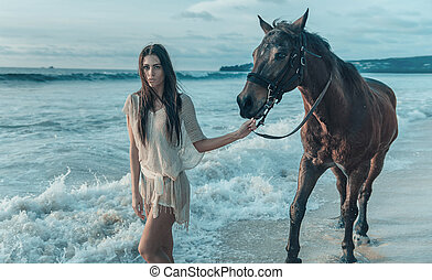 Brunette lady walking with a horse