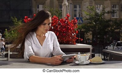 Brunette lady works with tablet while she sits in the restaurant before red flowers