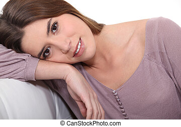 Brunette leaning head on sofa