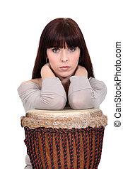 Brunette leaning on bongo drum