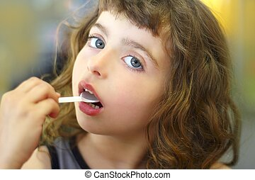 brunette little girl eating playing plastic spoon