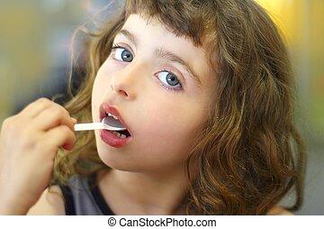 brunette little girl eating playing plastic spoon