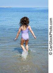 brunette little girl running into beach water