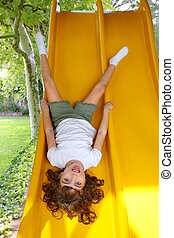 Brunette little girl upside down playground slide