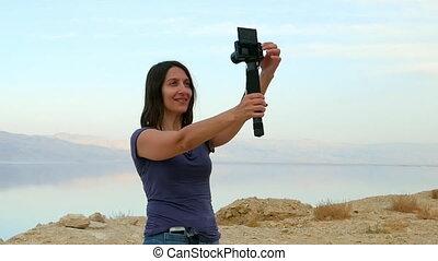 Brunette longhair woman takes selfie in mountains - Brunette...