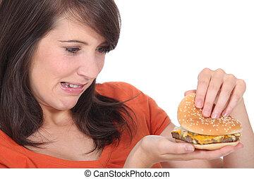 brunette looking at burger
