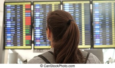 brunette looks at departures schedule in airport terminal - ...