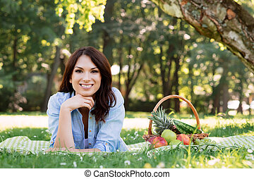 Brunette lying on a mat with basket full of fruits in the park