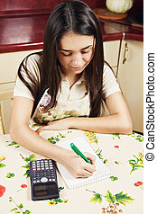 Brunette making calculations - Young caucasian brunette...