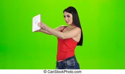 Brunette making photo using a tablet pc. Green screen studio