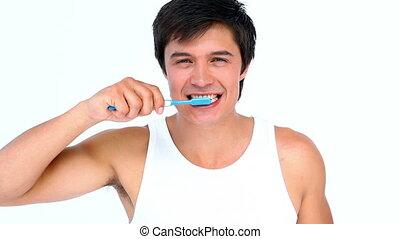 Brunette man brushing his teeth against white background