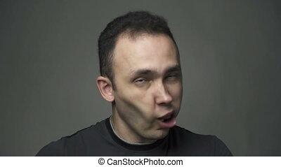 Brunette man shaking tongue, slow motion video