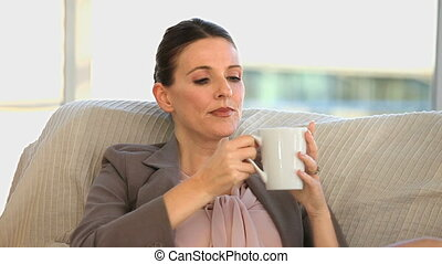 Brunette middle aged lady drinking a cup of coffee