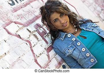 Brunette Model - A brunette model against a brick wall in an...