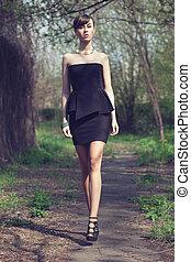 brunette model posing in short black dress
