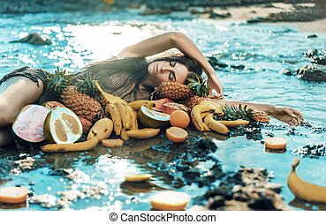 Brunette model posing with lots of healthy tropical fruit