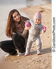 Brunette mom helping small daughter to walk on beach