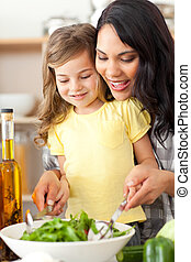 Brunette mother helping her daughter prepare salad