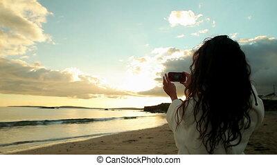 brunette, nemen van een foto, van, de, ondergaande zon