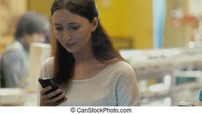 Brunette oman using smartphone in cafe - Smiling brunette...