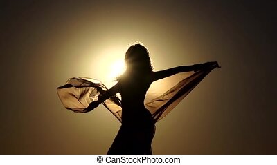 Brunette on the sunset makes graceful movements. Slow...