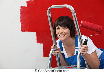 Brunette painting wall in red
