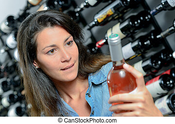 Brunette picking out a bottle of wine