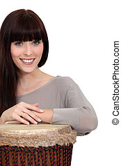 Brunette playing bongo drum