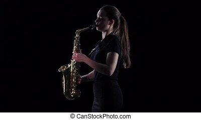 Brunette plays on saxophone in slow motion. Black studio background