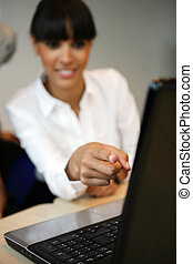 Brunette pointing at a laptop