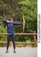Brunette practicing archery - Focused brunette practicing...
