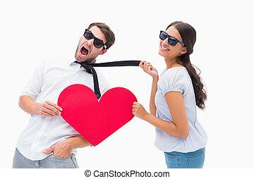 Brunette pulling her boyfriend by the tie holding heart on...
