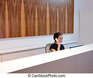 Brunette receptionist young woman in desk