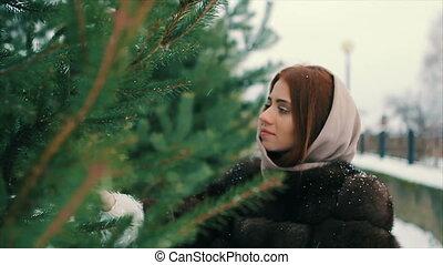 Brunette rich woman waist coat of brown fur near Christmas tree slow motion