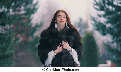 Brunette rich woman waist coat of brown fur on background of Christmas tree slow motion