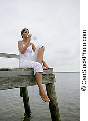 Brunette sat on jetty with bottle of water