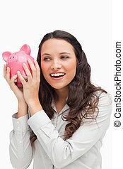 Brunette shaking a piggy bank