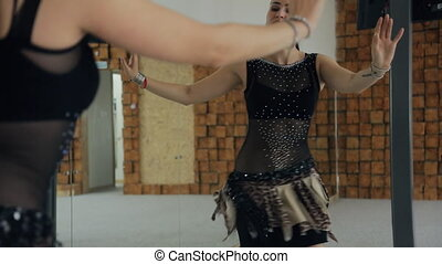 Brunette shows oriental dance in front of mirror in dancing class.