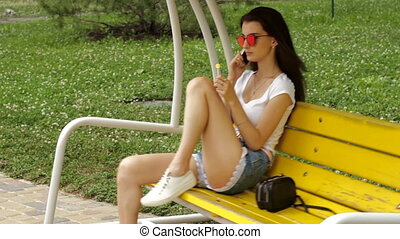 brunette sits on a swing on the phone and sucks lollipop