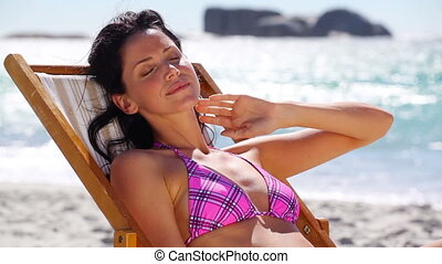 Brunette sitting on a deck chair on the beach
