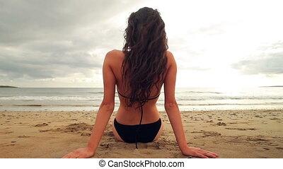 Brunette sitting on the beach