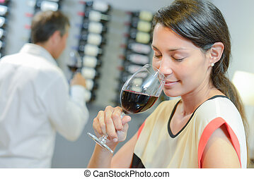Brunette smelling a glass of red wine