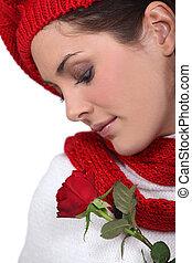 Brunette smelling rose