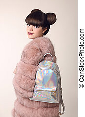 Brunette smiling teen girl in pink fur coat advertise backpack, young stylish beautiful woman. Fashion Hologram Laser Back pack Female Student.