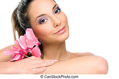 Brunette spa beauty with pink flowers