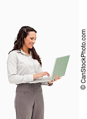 Brunette standing while using a laptop