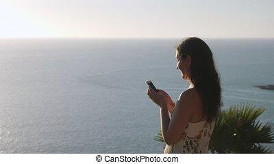 brunette stands on blue ocean coastline edge and types - ...